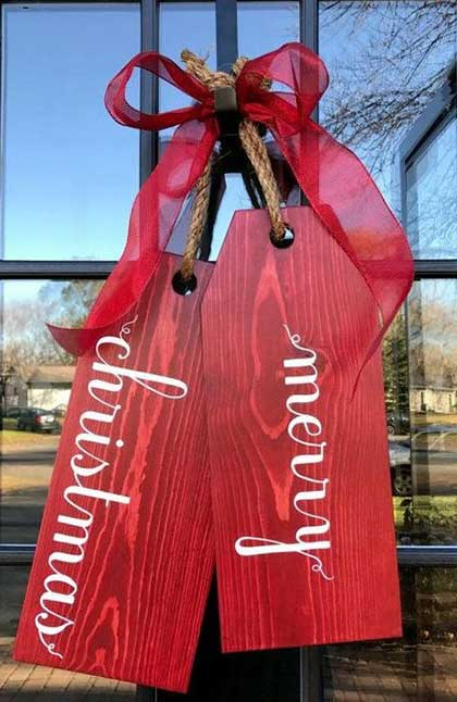 Wood door tags that say Merry Christmas hanging on the outside of a front door