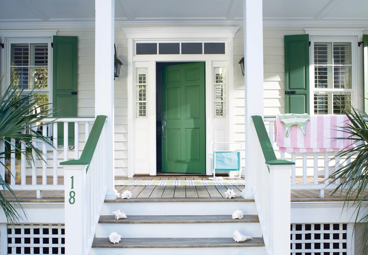 grand entrance of green door with white porch